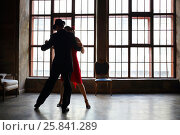 Woman in red dress and man in black suit dance tango near big window in room. Стоковое фото, фотограф Losevsky Pavel / Фотобанк Лори