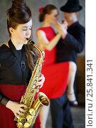 Купить «Pretty girl playing saxophone next to dancing pair, focus on musician», фото № 25841341, снято 4 июня 2015 г. (c) Losevsky Pavel / Фотобанк Лори