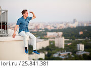 Купить «Young man in denim clothes looks afar, sitting on the edge of the roof and having put a hand as a peak to a forehead», фото № 25841381, снято 4 июня 2015 г. (c) Losevsky Pavel / Фотобанк Лори