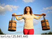 Купить «Portrait of a woman with a yoke and wooden pails against the blue sky», фото № 25841445, снято 18 июля 2015 г. (c) Losevsky Pavel / Фотобанк Лори