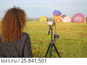 Купить «Woman with luxuriant hair shoot at the camera the rise of balloons on the field», фото № 25841501, снято 19 июля 2015 г. (c) Losevsky Pavel / Фотобанк Лори