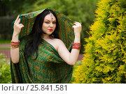 Купить «Brunette woman in sari and Indian adornment poses to green bush in park», фото № 25841581, снято 19 июля 2015 г. (c) Losevsky Pavel / Фотобанк Лори