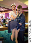 Купить «Young man holding woman in retro dress hugging at the bar», фото № 25841609, снято 18 января 2015 г. (c) Losevsky Pavel / Фотобанк Лори