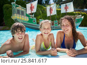 Купить «Young woman and two children lie on edge of swimming pool and smile», фото № 25841617, снято 5 августа 2016 г. (c) Losevsky Pavel / Фотобанк Лори
