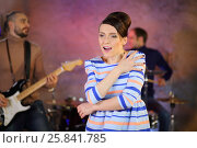 Купить «Beautiful retro singer sings a song with feeling near musicians», фото № 25841785, снято 9 декабря 2014 г. (c) Losevsky Pavel / Фотобанк Лори