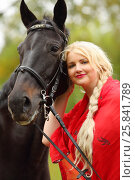 Купить «Woman in red dress and blond hair stands near horse in park», фото № 25841789, снято 13 сентября 2015 г. (c) Losevsky Pavel / Фотобанк Лори