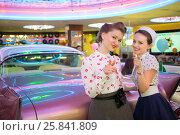 Купить «Two beautiful girls in retro dress gesture and have a fun at the», фото № 25841809, снято 18 января 2015 г. (c) Losevsky Pavel / Фотобанк Лори