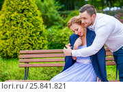Woman sits on bench, man puts his jacket for girl in green summer park. Стоковое фото, фотограф Losevsky Pavel / Фотобанк Лори