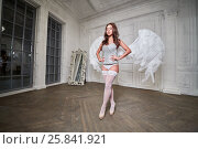 Купить «Young woman in white underwear, stockings and angel wings behind her back walks along room with her hands akimbo», фото № 25841921, снято 10 июня 2016 г. (c) Losevsky Pavel / Фотобанк Лори