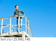 Купить «Young man in denim wear stands on metal construction against blue sky and looks into the distance», фото № 25842145, снято 12 июня 2015 г. (c) Losevsky Pavel / Фотобанк Лори