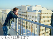 Купить «Young man in denim clothes stands on the building roof leaning to the fencing», фото № 25842217, снято 12 июня 2015 г. (c) Losevsky Pavel / Фотобанк Лори