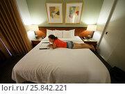 Купить «Woman lies on a bed in hotel room», фото № 25842221, снято 2 сентября 2014 г. (c) Losevsky Pavel / Фотобанк Лори