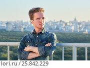 Купить «Portrait of young man in denim clothes stands crossing arms on chest on the roof leaning his back to the railing», фото № 25842229, снято 12 июня 2015 г. (c) Losevsky Pavel / Фотобанк Лори