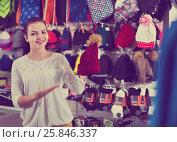 Купить «Female customer examining knit caps in sports store», фото № 25846337, снято 22 ноября 2016 г. (c) Яков Филимонов / Фотобанк Лори