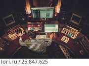 Купить «Sound engineer working in boutique recording studio.», фото № 25847625, снято 20 января 2018 г. (c) Andrejs Pidjass / Фотобанк Лори