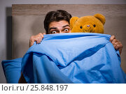 Young man scared in bed. Стоковое фото, фотограф Elnur / Фотобанк Лори