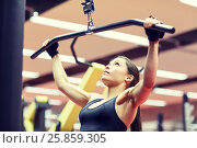 Купить «woman flexing arm muscles on cable machine in gym», фото № 25859305, снято 12 декабря 2015 г. (c) Syda Productions / Фотобанк Лори
