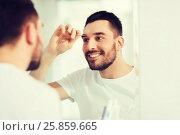 Купить «man with tweezers tweezing eyebrow at bathroom», фото № 25859665, снято 15 января 2016 г. (c) Syda Productions / Фотобанк Лори