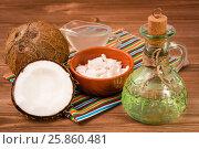Кокосовое масло в бутылке, кокосовое молоко и кокосы на деревянном столе. Стоковое фото, фотограф Елена Руй / Фотобанк Лори