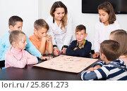 Купить «Female and happy kids sitting at table with board game», фото № 25861273, снято 5 ноября 2016 г. (c) Яков Филимонов / Фотобанк Лори