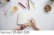 Купить «woman drawing picture in notebook at home desk», видеоролик № 25861529, снято 22 марта 2017 г. (c) Syda Productions / Фотобанк Лори