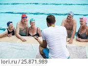 Купить «Male instructor assisting senior swimmers at poolside», фото № 25871989, снято 12 декабря 2016 г. (c) Wavebreak Media / Фотобанк Лори