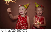 Купить «Two charming little sisters twins in holiday caps with sparkling Bengal lights in their hands having fun on a holiday», видеоролик № 25887073, снято 12 января 2017 г. (c) Mikhail Davidovich / Фотобанк Лори