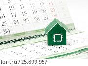 Купить «Картонный зеленый домик на фоне календаря», фото № 25899957, снято 27 марта 2017 г. (c) Наталья Осипова / Фотобанк Лори