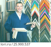 Купить «portrait of man in uniform choosing framing moulding in studio», фото № 25900537, снято 19 января 2019 г. (c) Яков Филимонов / Фотобанк Лори