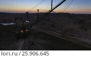 Купить «Boom of a walking excavator. Panorama. Sunset. Mine. View from the drone.», видеоролик № 25906645, снято 15 марта 2017 г. (c) Вячеслав Позднышев / Фотобанк Лори