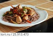 Гречневая лапша на белой тарелке с красной рыбой и овощами на кухонном столе. Стоковое фото, фотограф Галина Жигалова / Фотобанк Лори