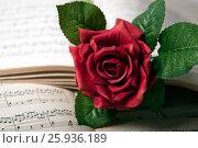 Купить «Rose flower lies on the music book», фото № 25936189, снято 8 апреля 2017 г. (c) Александр Калугин / Фотобанк Лори