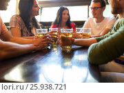 Купить «friends drinking beer at bar or pub», фото № 25938721, снято 14 июля 2016 г. (c) Syda Productions / Фотобанк Лори