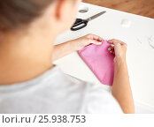 Купить «woman with needle stitching fabric pieces», фото № 25938753, снято 29 сентября 2016 г. (c) Syda Productions / Фотобанк Лори