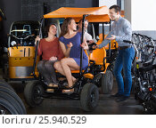 Купить «Male employee helping family to select tour electrics», фото № 25940529, снято 16 октября 2018 г. (c) Яков Филимонов / Фотобанк Лори
