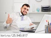 Купить «Smiling young male happy to book hotel online», фото № 25940817, снято 5 марта 2017 г. (c) Яков Филимонов / Фотобанк Лори