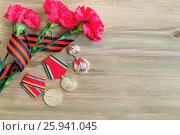 Купить «9 мая, композиция - юбилейные медали в честь Победы, три красные гвоздики и георгиевской ленточка. Открытка на День Победы», фото № 25941045, снято 2 апреля 2017 г. (c) Зезелина Марина / Фотобанк Лори