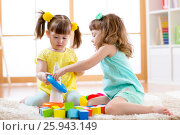 Купить «Children playing together. Toddler kid and baby play with blocks. Educational toys for preschool and kindergarten child. Little girls build pyramid toys at home or daycare.», фото № 25943149, снято 5 апреля 2017 г. (c) Оксана Кузьмина / Фотобанк Лори