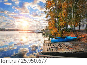Купить «A blue boat on the Volga River in the town of Plyos near the wooden pier and a luxurious white yacht in the distance on a sunny autumn day», фото № 25950677, снято 21 сентября 2012 г. (c) Baturina Yuliya / Фотобанк Лори