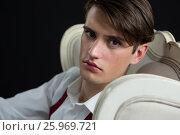 Купить «Androgynous man sitting on chair against black background», фото № 25969721, снято 15 декабря 2016 г. (c) Wavebreak Media / Фотобанк Лори