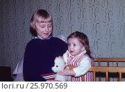 1976 год, Москва. Счастливое детство. Старшая девочка играет с маленькой сестрой. Редакционное фото, фотограф Наталия Преображенская / Фотобанк Лори