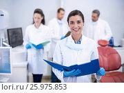 Купить «Smiling dentist holding file at dental clinic», фото № 25975853, снято 11 декабря 2016 г. (c) Wavebreak Media / Фотобанк Лори