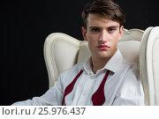 Купить «Androgynous man sitting on chair against black background», фото № 25976437, снято 15 декабря 2016 г. (c) Wavebreak Media / Фотобанк Лори