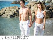 Купить «Couple holding hands while walking on shore», фото № 25980277, снято 17 января 2017 г. (c) Wavebreak Media / Фотобанк Лори
