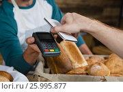 Купить «Customer paying bill through smartphone using NFC technology at counter», фото № 25995877, снято 27 января 2017 г. (c) Wavebreak Media / Фотобанк Лори