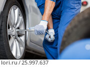 Купить «mechanic with screwdriver changing car tire», фото № 25997637, снято 1 июля 2016 г. (c) Syda Productions / Фотобанк Лори
