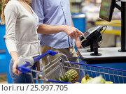 Купить «couple buying food at grocery self-checkout», фото № 25997705, снято 21 октября 2016 г. (c) Syda Productions / Фотобанк Лори