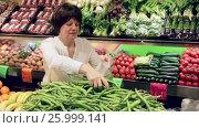 Купить «Mature woman buying green beans at market», видеоролик № 25999141, снято 23 марта 2017 г. (c) Яков Филимонов / Фотобанк Лори