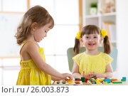 Купить «Kids playing with logical toy on desk in nursery room or kindergarten. Children arranging and sorting shapes, colors and sizes.», фото № 26003873, снято 5 апреля 2017 г. (c) Оксана Кузьмина / Фотобанк Лори