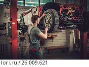 Mechanic working on classic car wheels and suspension in restoration workshop, фото № 26009621, снято 6 апреля 2017 г. (c) Andrejs Pidjass / Фотобанк Лори